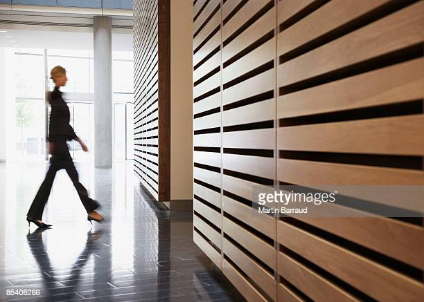 businesswoman walking in corridor - arrival photos stock photos and pictures