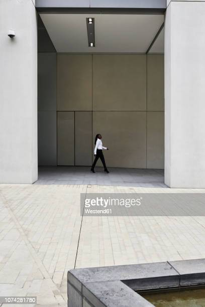 Businesswoman walking in front of a modern office building