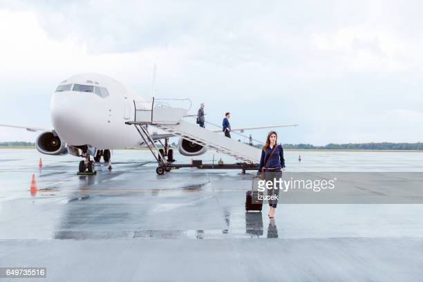 Businesswoman walking in front of airplane at the airport
