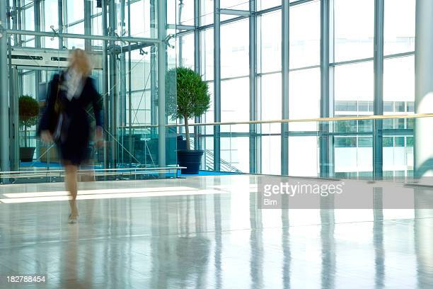 Businesswoman Walking in Lobby of an Office Building, Blurred Motion
