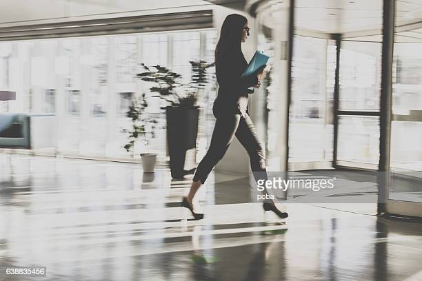 businesswoman walking in lobby - revolve stock photos and pictures