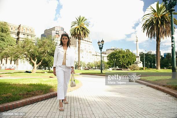 Businesswoman walking in park carrying handbag, portrait