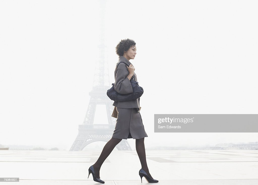 Businesswoman walking in plaza by Eiffel Tower : Stock Photo