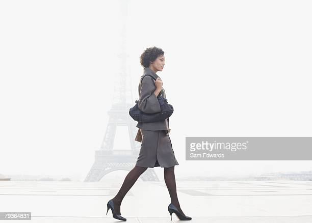 Businesswoman walking in plaza by Eiffel Tower