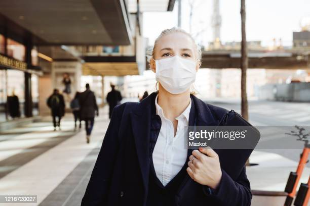 businesswoman walking in street wearing face mask - pandemic illness stock pictures, royalty-free photos & images
