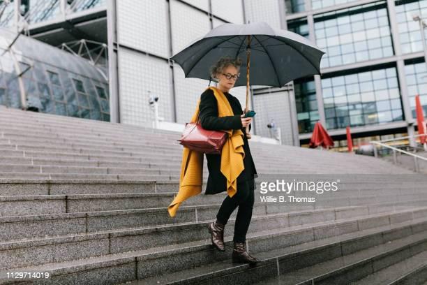 businesswoman walking in the rain - regenschirm stock-fotos und bilder