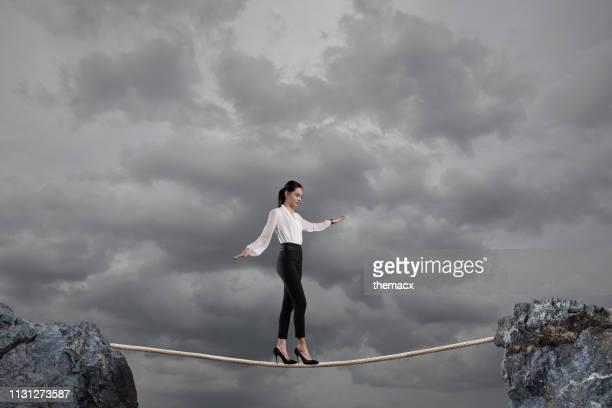 ロープの上を歩くビジネスウーマン - 綱渡りのロープ ストックフォトと画像