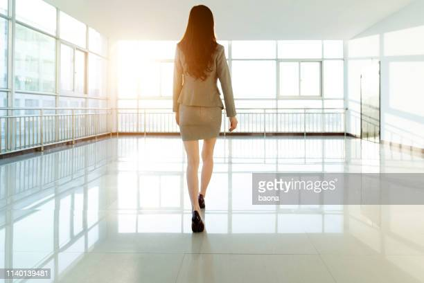 businesswoman walking on empty office - ankle length stock pictures, royalty-free photos & images