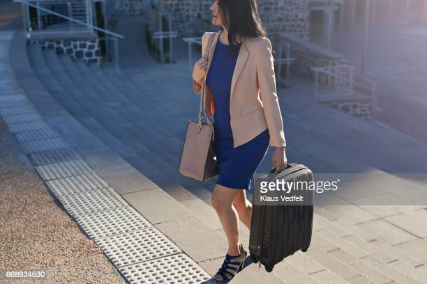 Businesswoman walking on staircase holding suitcase