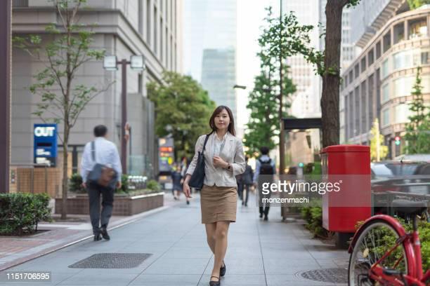 通りを歩いているビジネスウーマン - 丸の内 ストックフォトと画像