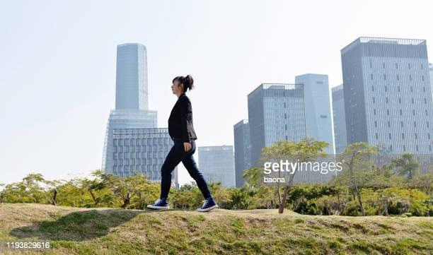 femme d'affaires marchant sur la colline de ville - blazer vert photos et images de collection