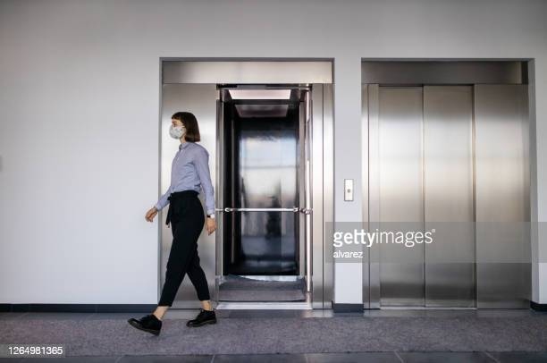 businesswoman walking out from elevator at office lobby - arrival stock pictures, royalty-free photos & images
