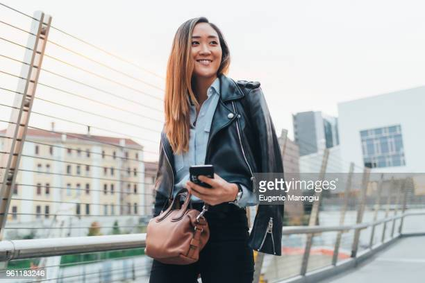 Businesswoman walking outdoors, holding smartphone, smiling