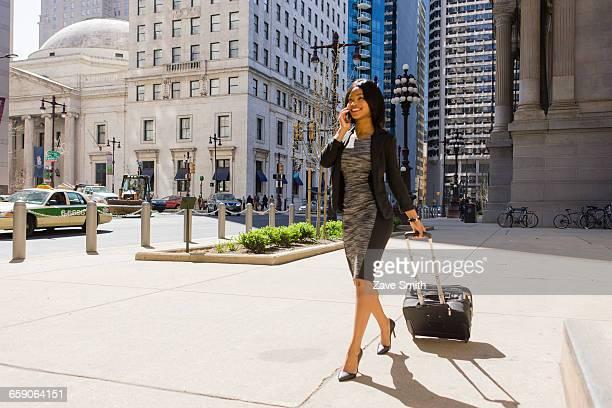 Businesswoman walking outdoors, pulling wheeled suitcase, using smartphone