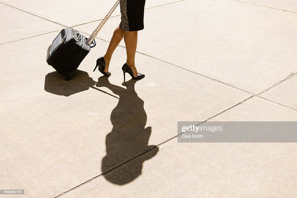 Businesswoman walking outdoors, wearing high heeled shoes, pulling wheeled suitcase, low section : Stock Photo