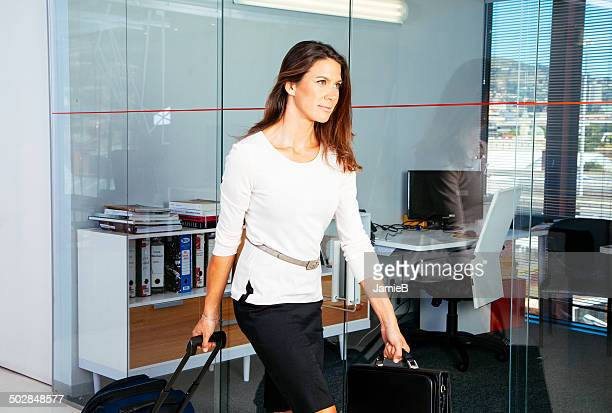 businesswoman walking through office with suitcase - wheeled luggage stock photos and pictures
