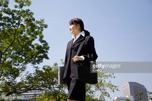 Businesswoman walking through park with shoulder bag and laptop