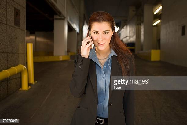 businesswoman walking through parkade talking on cell phone - approaching stock pictures, royalty-free photos & images