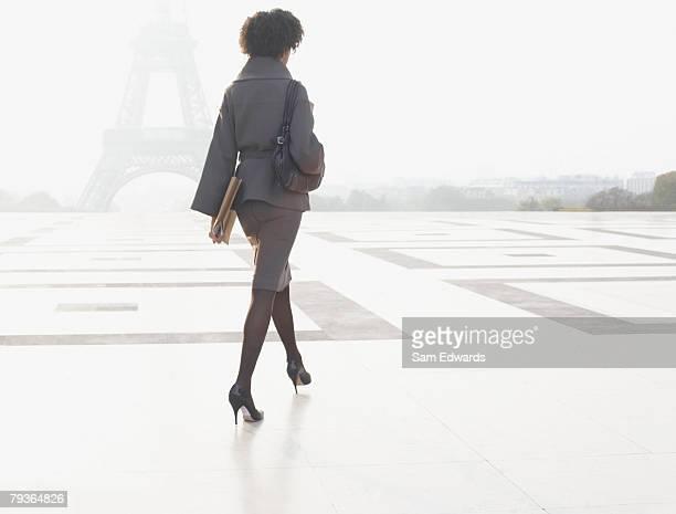 Businesswoman walking through plaza near Eiffel Tower