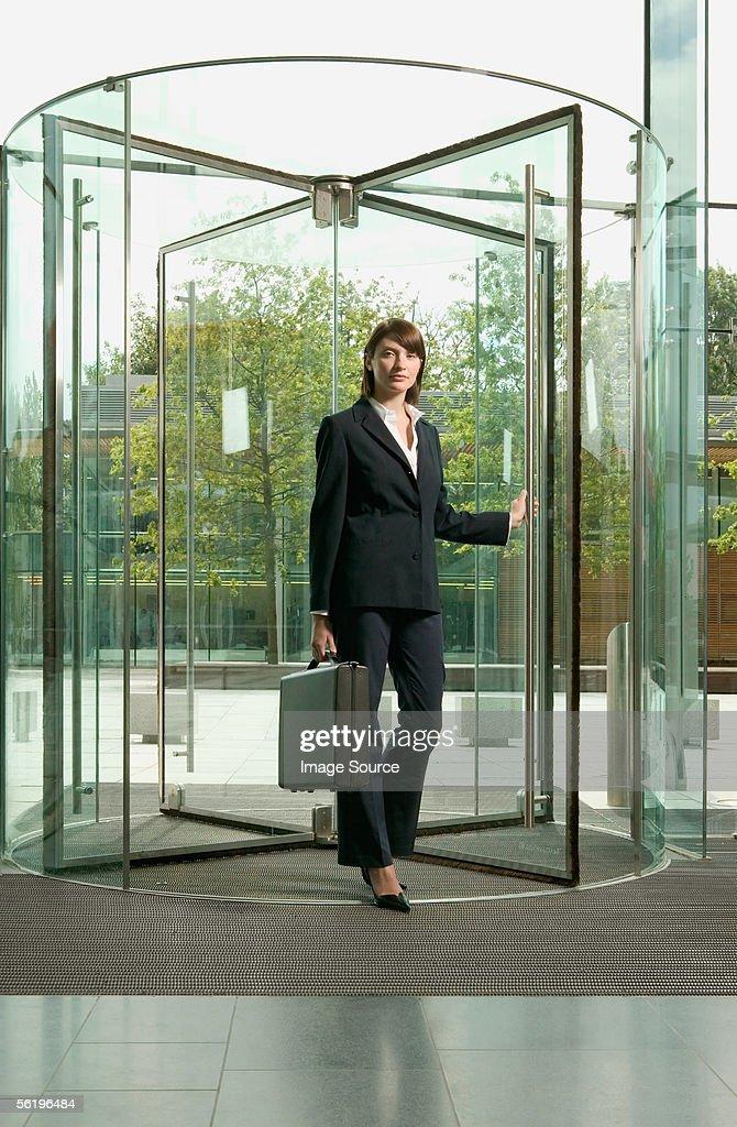 Businesswoman walking through revolving door : Stock Photo