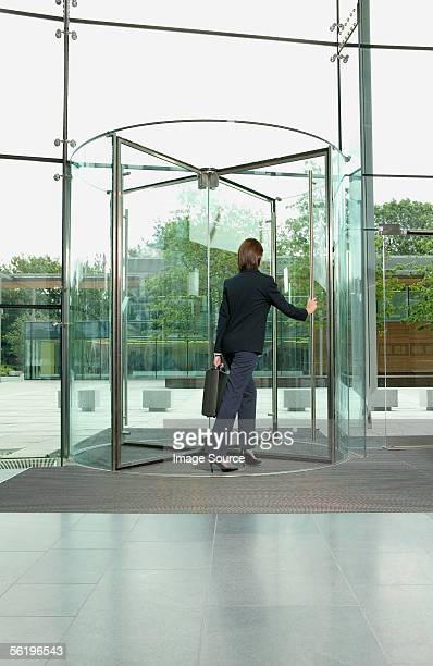 Businesswoman walking through revolving door