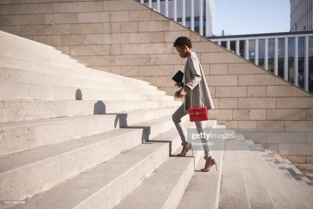 Businesswoman walking up stairs : Stock Photo