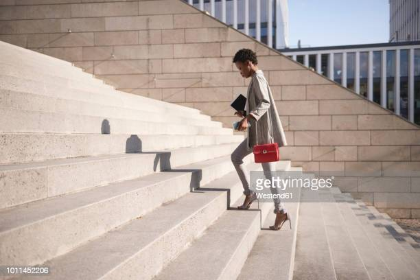 businesswoman walking up stairs - hoge hakken stockfoto's en -beelden