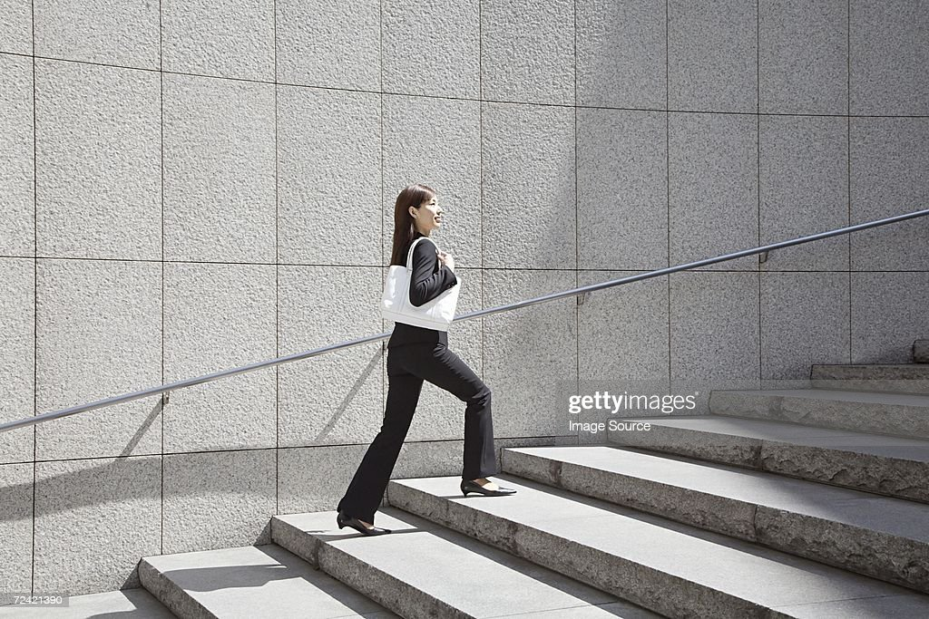 Businesswoman walking up steps : Stock Photo