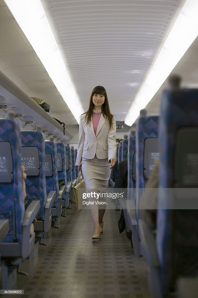 Businesswoman Walking up the Aisle of a Train : Stock Photo