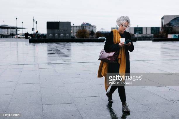 businesswoman walking with coffee - schwarze handtasche stock-fotos und bilder