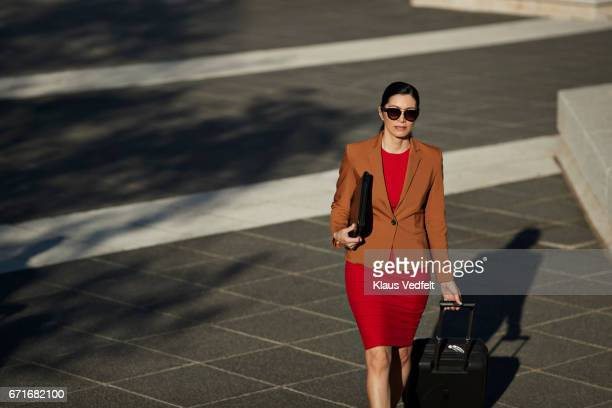 Businesswoman walking with rolling suitcase on big square