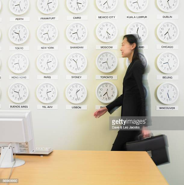 Businesswoman walking with time zone clocks on the wall behind her