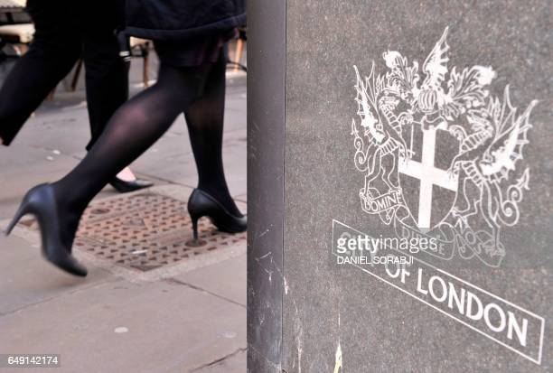 Businesswoman walks by a sign displaying the heraldic achievement of the City of London on March 7, 2017. - Britain's Finance minister Philip Hammond...