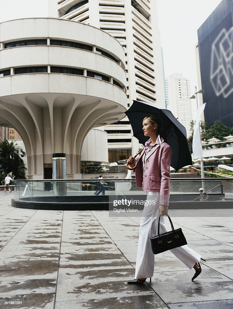 Businesswoman Walks in a Town Square Holding an Umbrella : Stock Photo