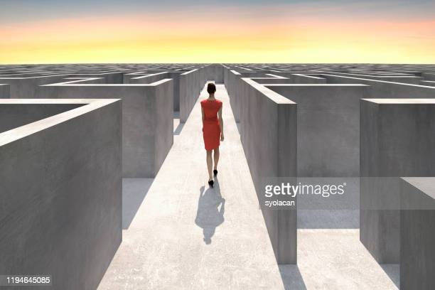 businesswoman walks inside of a complex maze - maze stock pictures, royalty-free photos & images