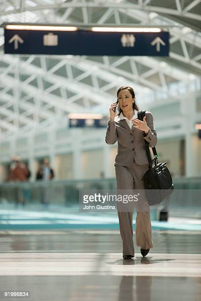 Businesswoman walks through airport while on phone