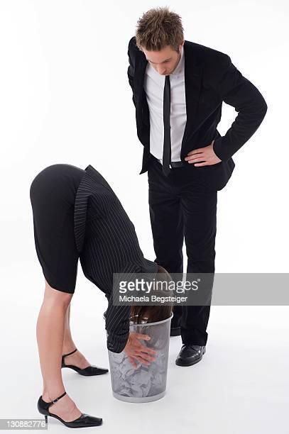 Businesswoman watching businesswoman sticking her head in a bin