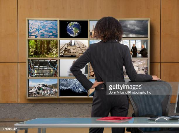 Businesswoman watching collage screen in office