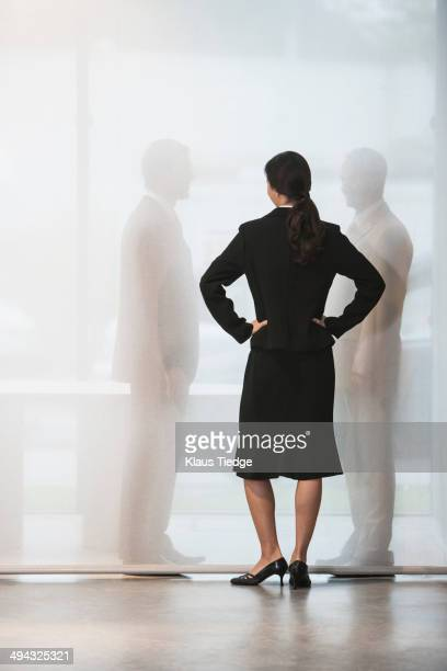 Businesswoman watching colleagues shake hands behind curtain