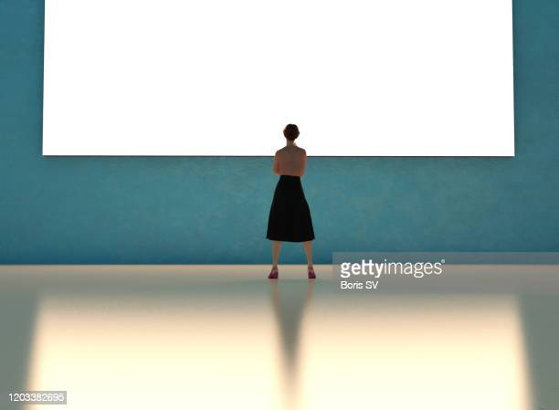 businesswoman watching large monitor - chairperson stock pictures, royalty-free photos & images