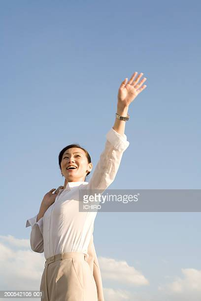 Businesswoman waving and smiling outdoors, low angle view