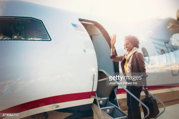 Businesswoman waving on airplane staircase