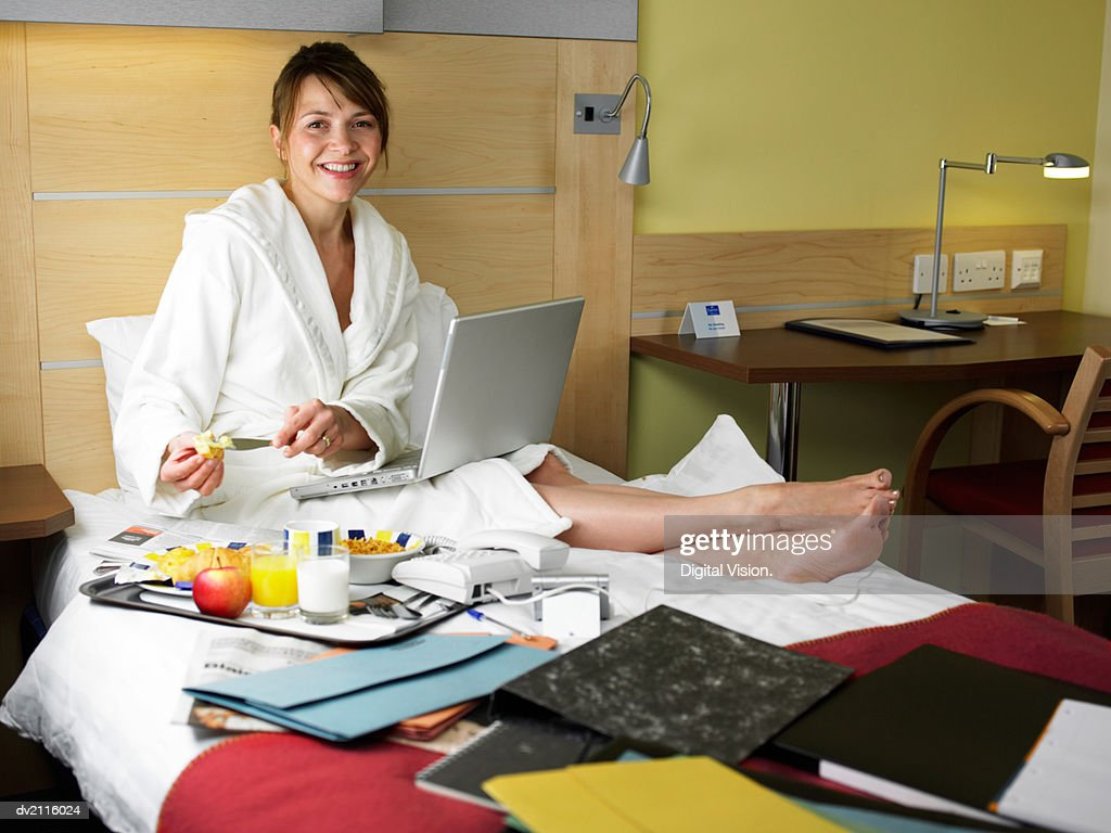 Businesswoman Wearing a Dressing Gown and With a Laptop in a Hotel Room : Stock Photo