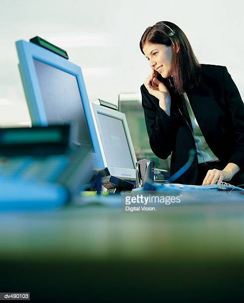 Businesswoman Wearing a Headset and Sitting on a Desk