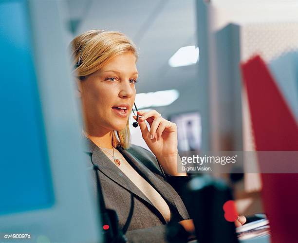 Businesswoman Wearing a Headset and Talking
