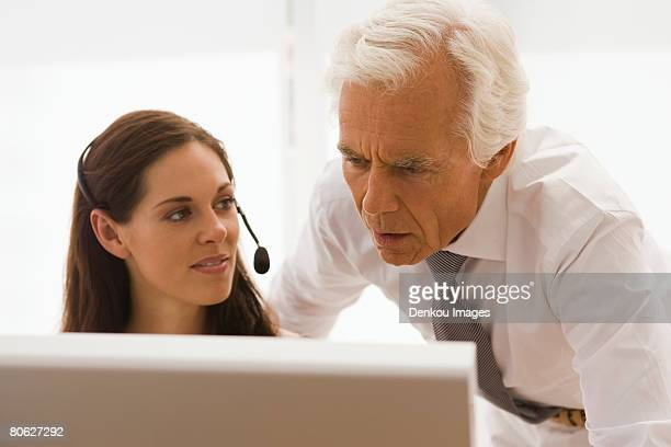 Businesswoman wearing a headset with a businessman looking at a computer monitor in an office