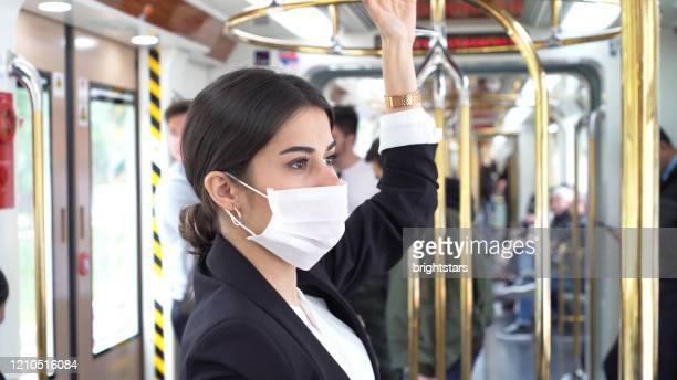 businesswoman wearing a mask while traveling - transporte público imagens e fotografias de stock