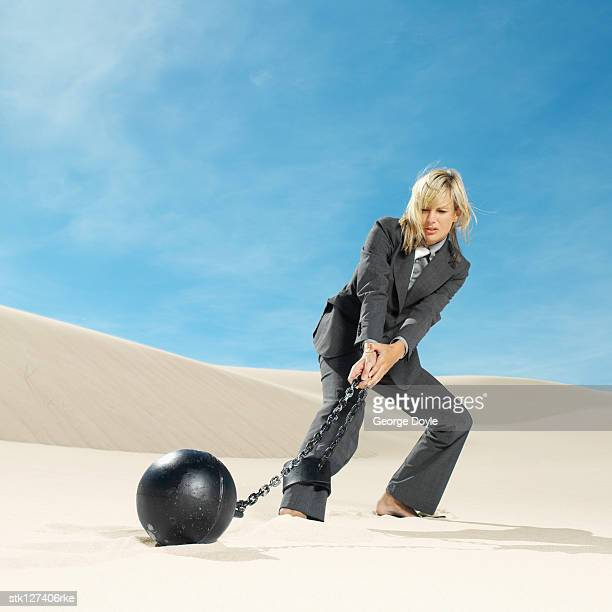 businesswoman wearing ball and chain in desert, low angle view