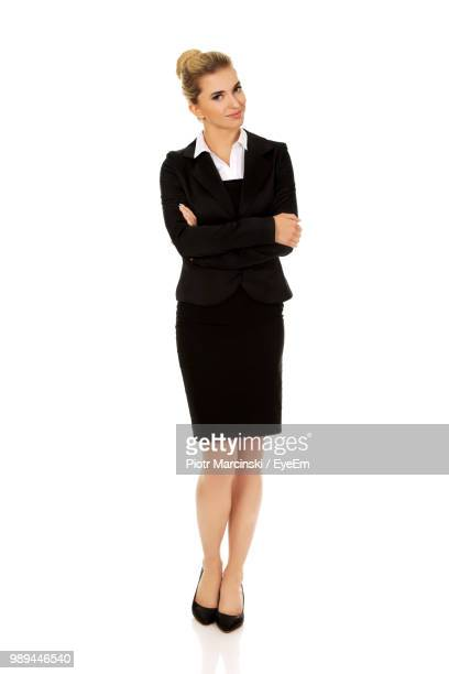 businesswoman wearing black suit while standing against white background - solo ragazze foto e immagini stock