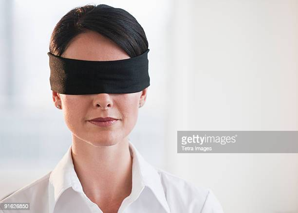 Businesswoman wearing blindfold